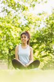 Full length of healthy young woman sitting on grass in park
