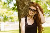 Portrait of beautiful young woman against tree in the park