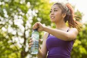 Portrait of healthy and beautiful young woman holding water bottle in park