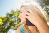 Fit blonde talking on her smartphone on a sunny day