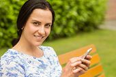 Smiling brunette using her smartphone on bench in the park