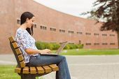 Happy brunette sitting on bench typing on laptop in the park