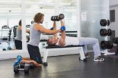 Side view of a male trainer assisting young man with dumbbells in the gym