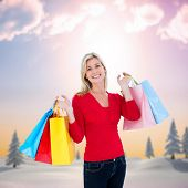 Happy blonde holding shopping bags against snowy landscape with fir trees