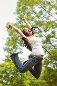 Excited brunette jumping in the park on a sunny day