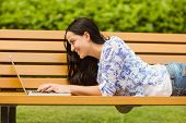 Happy brunette lying on bench using laptop in the park