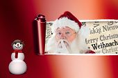 Santa asking for quiet to camera through tear in red paper