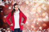 Smiling brunette posing with winter wear against light design shimmering on red
