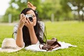 Brunette lying on grass taking picture in the park