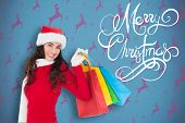 Festive brunette in winter wear holding shopping bags against blue and purple reindeer pattern