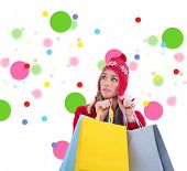 Blonde in winter clothes holding shopping bags against dot pattern