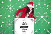 Festive brunette pointing white poster against snowflake wallpaper pattern