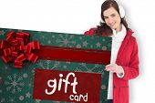 Happy brunette showing gift card against white background with vignette