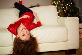 Happy redhead lying on the couch at christmas at home in the living room