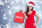 Festive brunette holding sale bag against snowflake design shimmering on blue