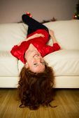 Pretty redhead lying on the couch at home in the living room