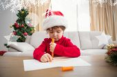 Festive little boy writing wish list against hanging decorations