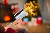 Woman holding credit card at christmas at home in the living room