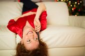 Happy redhead lying on the couch phoning at home in the living room