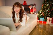 Smiling redhead woman using laptop on couch at christmas at home in the living room