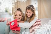 Mother opening christmas gift with daughter against snowflake frame
