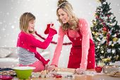 Festive mother and daughter making christmas cookies against twinkling stars