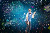 Geeky hipster dancing like a fool against colourful fireworks exploding on black background