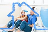 Charming couple relaxing after painting a room against house outline