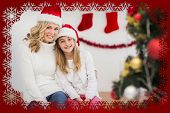 Festive mother and daughter smiling at camera against snowflake frame