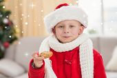 Festive little boy eating a cookie against snow