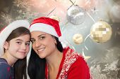 Mother and daughter in santa hats against hanging christmas decorations