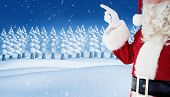 Mid section of santa pointing against snowy landscape with fir trees