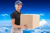Happy delivery woman holding cardboard box against mountain peak through clouds