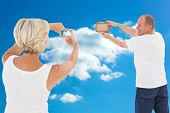 Mature couple hanging up picture frame against cloudy sky