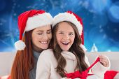 Mother and daughter opening gift against blurred snowy landscape
