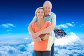 Happy older couple holding paint roller against mountain peak through clouds