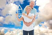 Happy older couple holding house shape against blue sky with white clouds