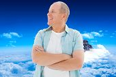 Happy older man with arms crossed against mountain peak through clouds