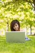 Relaxed young woman using laptop in the park