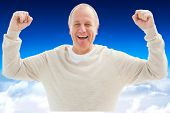 Happy mature man cheering at camera against blue sky over clouds