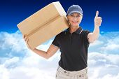 Happy delivery woman holding cardboard box against bright blue sky over clouds