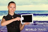 Beautiful businesswoman holding tablet PC and business card in front of screen. Seascape as backdrop