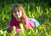 Cute little girl laying in green grass in the park.