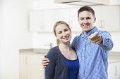 Happy Young Couple Holding Keys To New Home