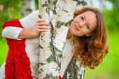 Beautiful Young Girl Looks Out From Behind A Birch