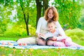 Mother Reads Her Daughter An Interesting Book In The Park