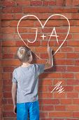 pic of initials  - Little boy in love drawing the heart with initials on wall - JPG