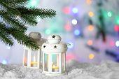 Lantern under Christmas tree on snow, on blurred background
