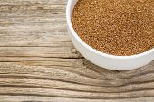 a small ceramic bowl of gluten free teff grain against weathered wood background