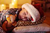Little boy sleeping near fireplace in room